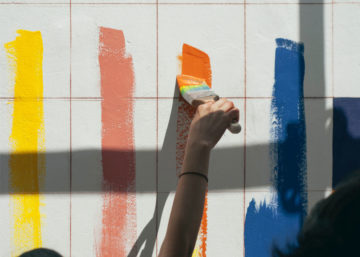 person painting orange stripe on white tiled wall with stripes of yellow, pink and blue already painted
